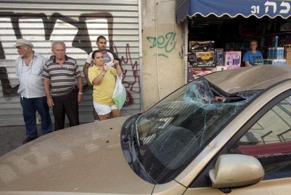 Varios israelíes inspeccionan los daños registrados en un coche por el l...