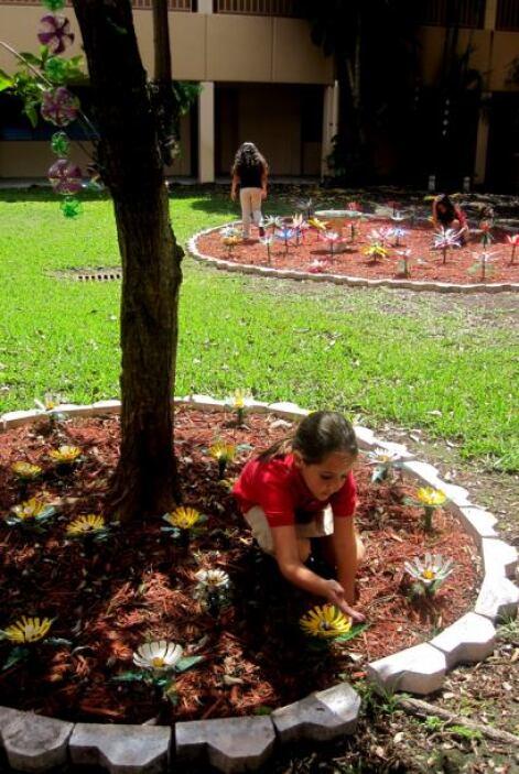 Una niña decora el jardín a la sombra de un árbol.