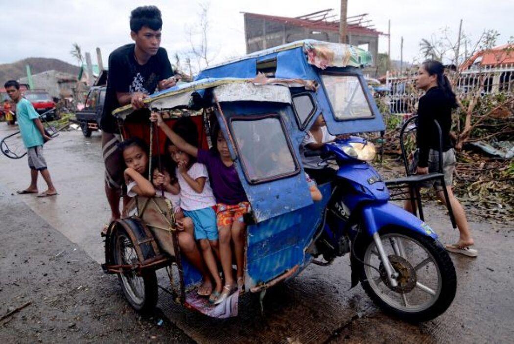 Varios niños viiajan en una moto a lo largo de una calle en una zona dev...