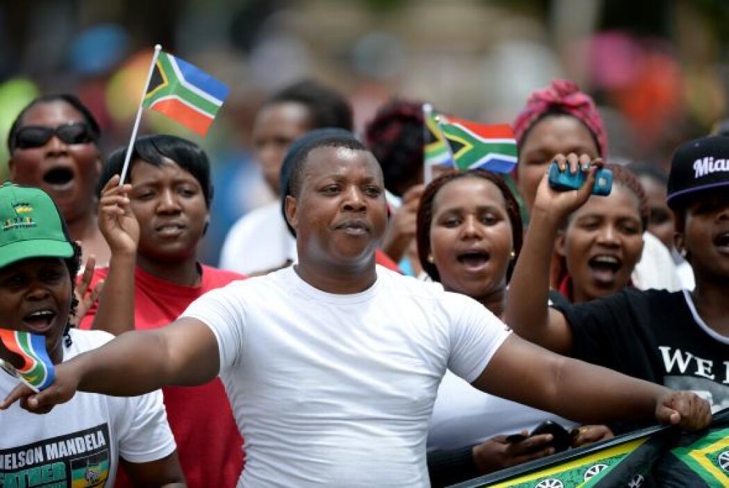 Un hombre despliega una enseña de Sudáfrica con el rostro de Mandela en...