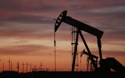 An oil pumpjack works at dawn in the Permian Basin oil field on January...