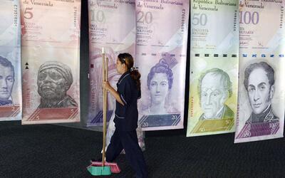 Una mujer camina frente a las réplicas gigantes de los billetes v...