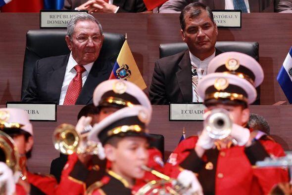 Raúl Castro y Rafael Correa observan la banda marcial durante la inaugur...