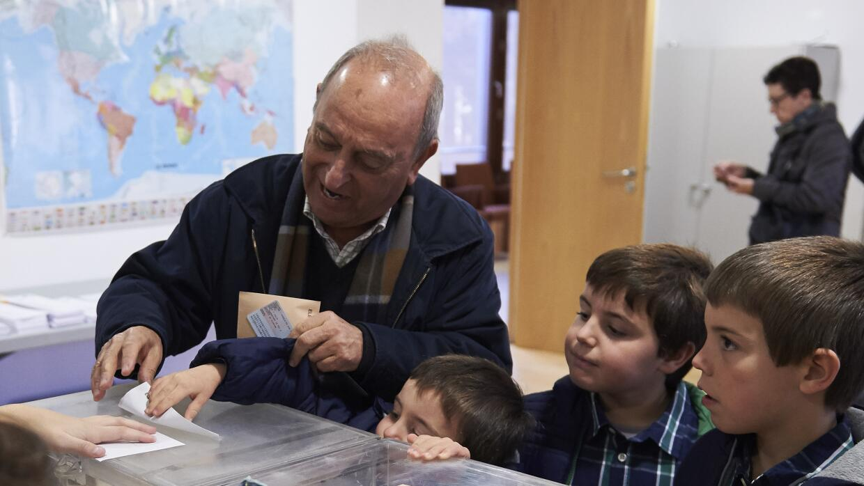 Un hombre vota con sus nietos.