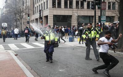 Oficiales de policía repelen a los manifestantes con gas pimienta...