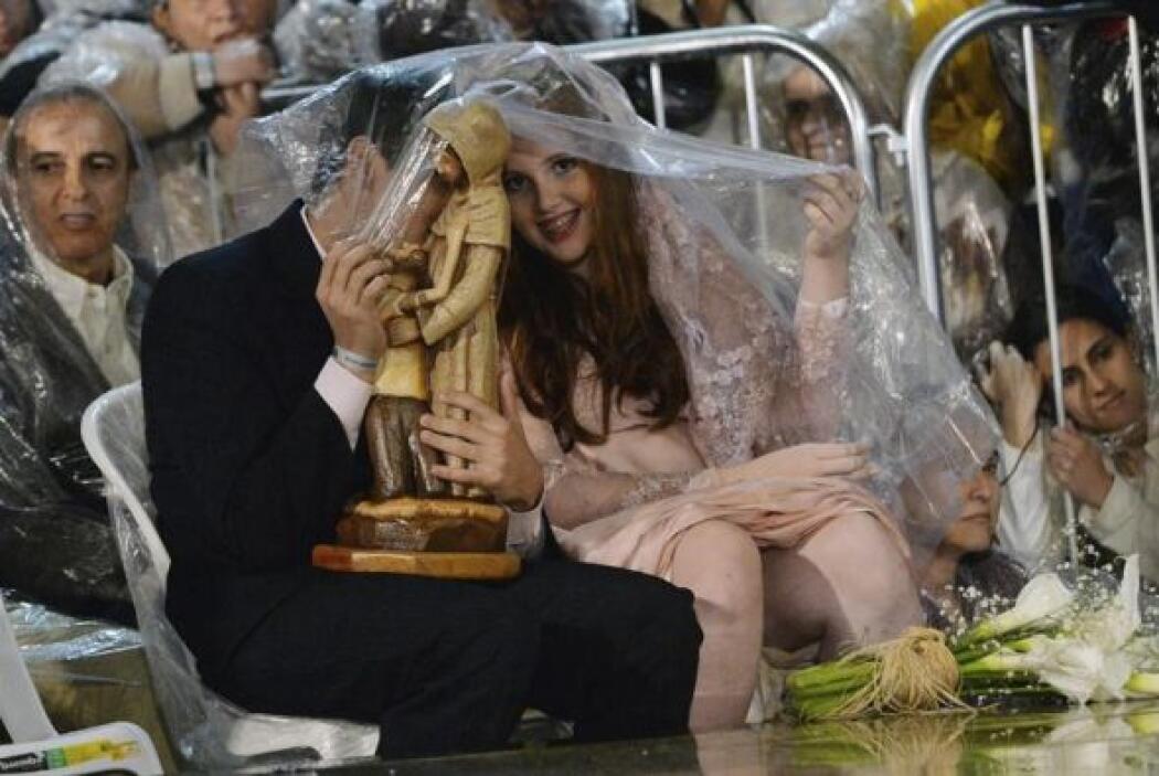 Una pareja de recién casados se protege de la lluvia con un plástico dur...