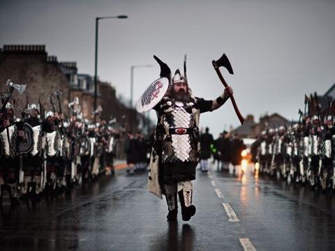 Lugareños vestidos como vikingos marchan por las calles de Lerwick, en l...