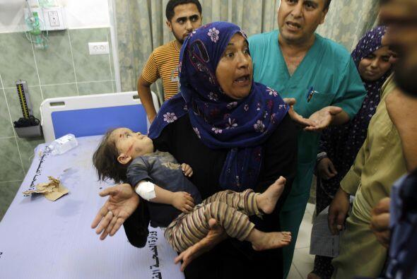 Una   mujer lleva a   un   niño herido   en   el hospital   al-  Najar...