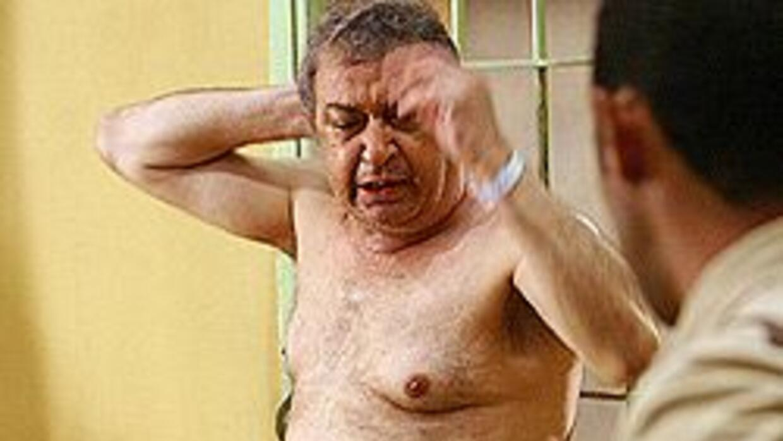 La foto muestra a un prisionero desnudo en un pasillo de Abu Ghraib mien...