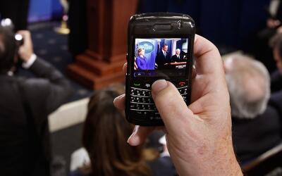 Un periodista usa una BlackBerry para tomar una foto del presidente Bara...