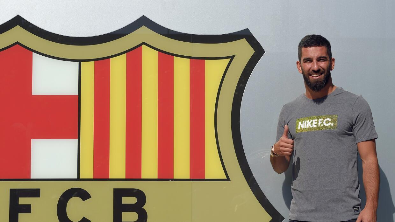 El jugador turco posó junto al escudo del FC Barcelona.