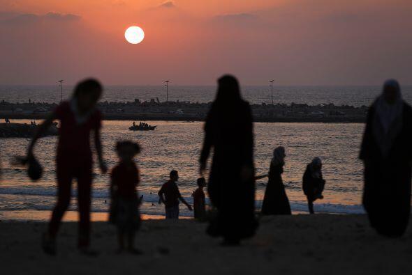 Familias palestinas caminan en la playa en la ciudad de Gaza después de...
