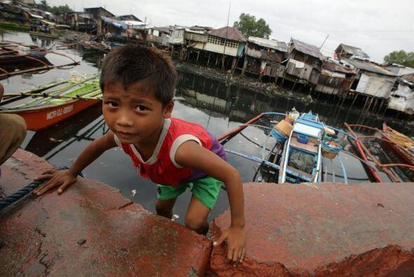 Un niño filipino escala un muro en una aldea costera en Las Pinas, sur d...