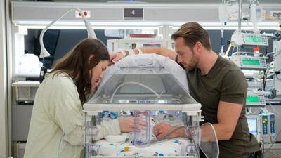 Danielle y Adam, los afortunados padres, observan con amor a una de las...