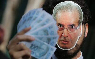 Un manifestante de la organización Avaaz trae puesta una máscara con la...