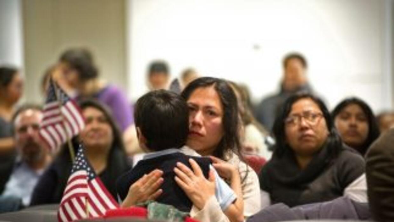 Una mujer inmigrante abraza a su hijo el día en que el presidente Barack...