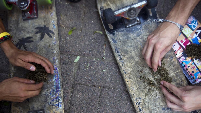 Dos jóvenes se hacen un cigarro de marihuana en Medellín.