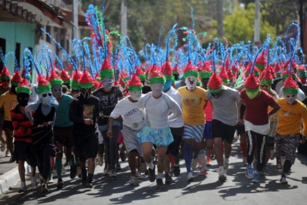 Los lugareños se colocan sombreros rojos y verdes y toman parte en la pr...