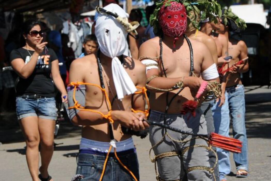 Un penitente carga una cruz a cuestas mientras otros se flagelan a si mi...