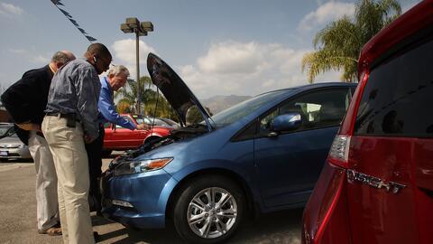 Un vendedor de autos Honda muestra un vehículo a potenciales clie...