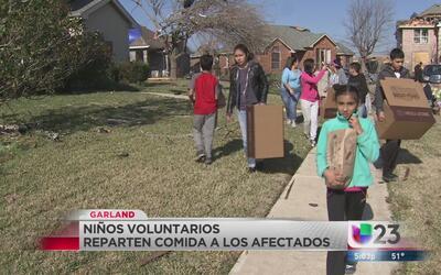 Niños voluntarios reparten comida en zona devastada por tornados