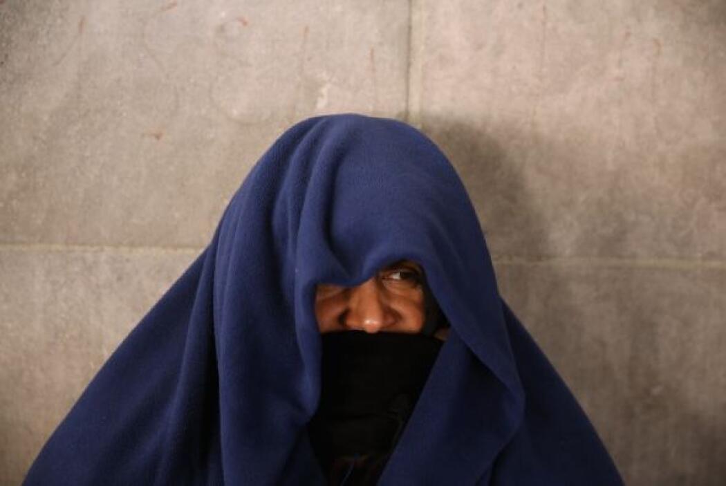 Un hombre sin hogar se cubre de la fría mañana en la estación del metro...