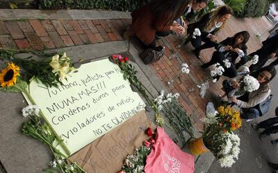 Un grupo de personas deja flores frente al edificio donde vive el supues...