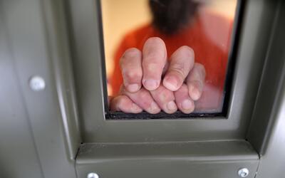 Un detenido de ICE se apoya en la ventana de una celda en un centro de d...