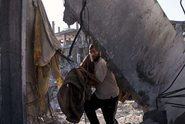 Un palestino lleva una alfombra a las ruinas de su casa.
