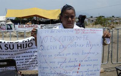 En Tetelcingo, una mujer exhibe una manta para su familiar desaparecido.