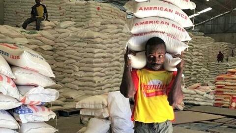 Un hombre carga un saco de arroz en un almacén de Puerto Pr&iacut...