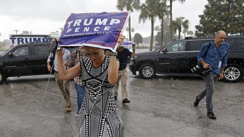 Una seguidora de Trump se protege de la lluvia a las afueras de su mitin...