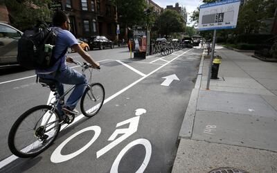 Un ciclista va por una ciclovía entre autos estacionados y la ace...