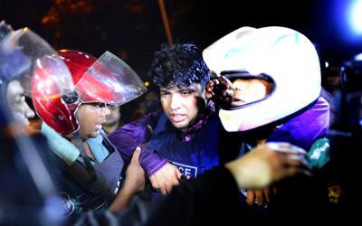 Un oficial de policía de Bangladesh es asistido por sus compañeros,  lue...