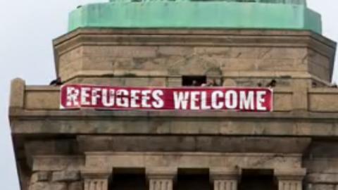 Cartel colocado en la Estatua de la Libertad que da la bienvenida a los...
