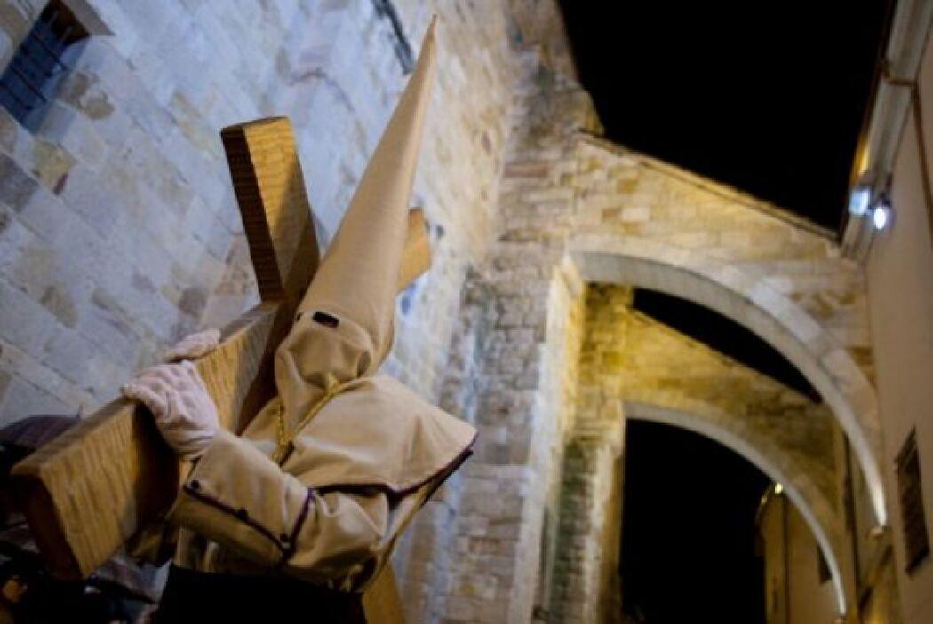 En Zamora, España, un penitente encapuchado carga una pesada cruz durant...