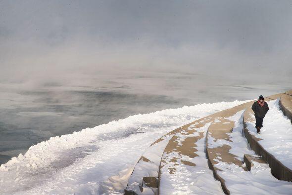 Un hombre camina a las orillas del lago Michigan, donde las temperaturas...