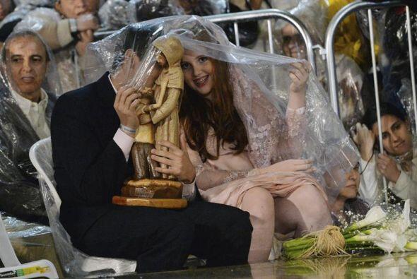 Una pareja de recién casados se protege de la lluvia con un pl&aa...