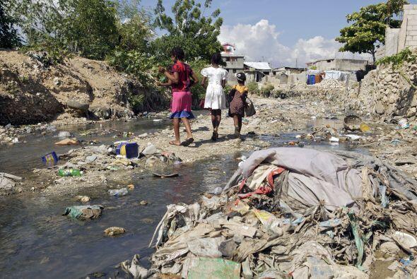 Algunos habitantes usan palas y carretillas para limpiar los terrenos. &...