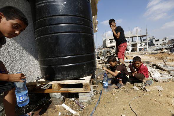 Niños palestinos llenans sus botellas de agua al regresar a su casa dest...