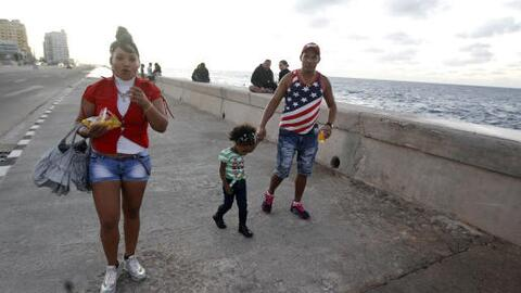 A family walks on the seafront in Havana on January 12, 2017, after the...