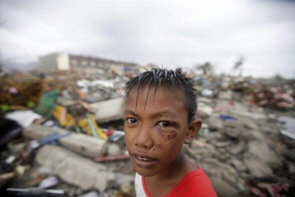 Un chico Filipino, entre las ruinas que dejó el tifón Haiyan tras su pas...