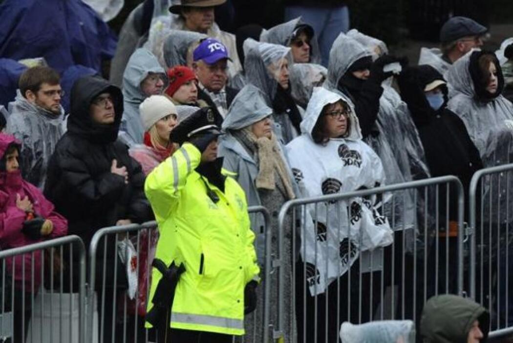 Decenas de asistentes desafían a la lluvia durante una ceremonia en memo...