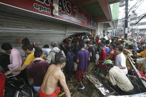 Gente forza la cortina de una tienda en la ciudad de Tacloban, en la pro...