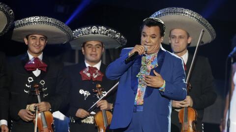 Juan Gabriel durante un concierto acompañado por mariachis.