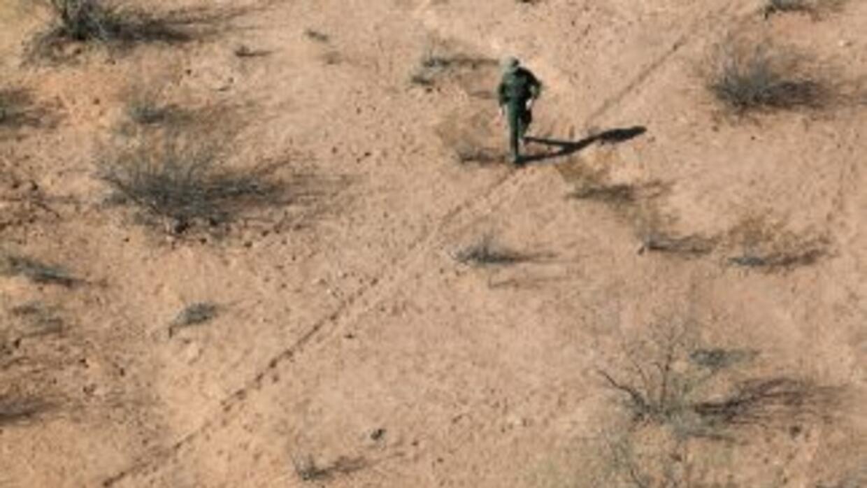 Una agente de la Patrulla Fronteriza revisa las huellas de indocumentado...