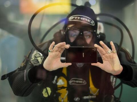 Un hombre tiene un teléfono inteligente impermeable en un tanque...