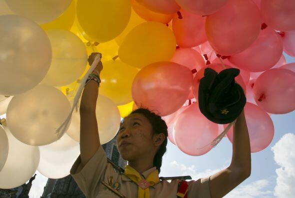 Una niña exploradora tailandesa sostiene globos en el templo Wat...