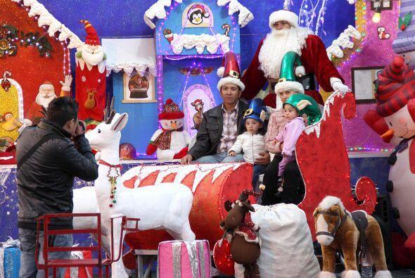 Una familia posa con Santa Claus en su trineo en la Ciudad de México.