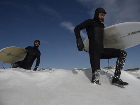 Unas personas se disponen a practicar surf en la playa de Rockaway, cubi...